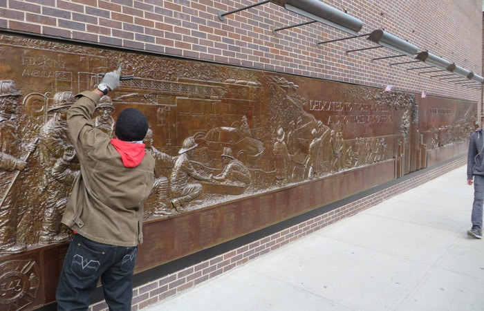 Placa homenaje a los bomberos de Nueva York fallecidos en el 11-S que es continuamente limpiada y pulida por el hombre de la imagen ferry a Staten Island