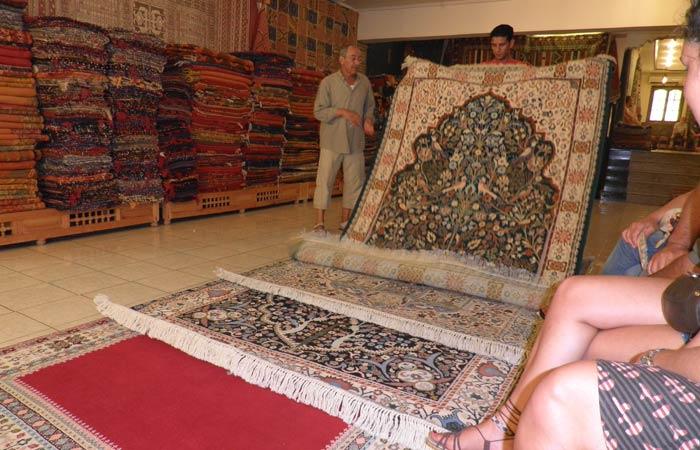 El dueño de la tienda de alfombras muestra el género un día en Tánger