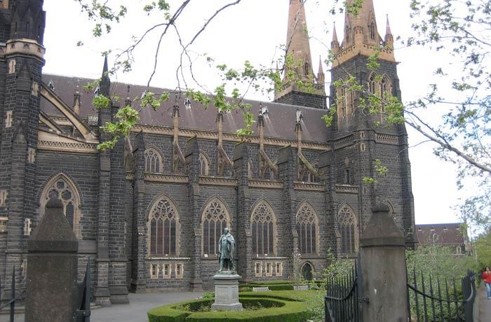 Costado izquierdo de la Catedral de San Patricio y estatua del irlandés Daniel O'Connell qué ver en Melbourne
