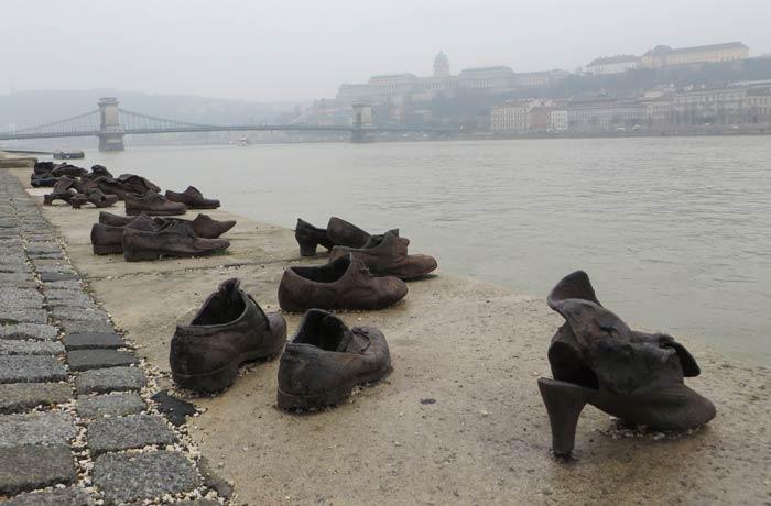 Detalle de los zapatos a la orilla del Danubio con el puente de Las Cadenas y el Castillo de Buda al fondo