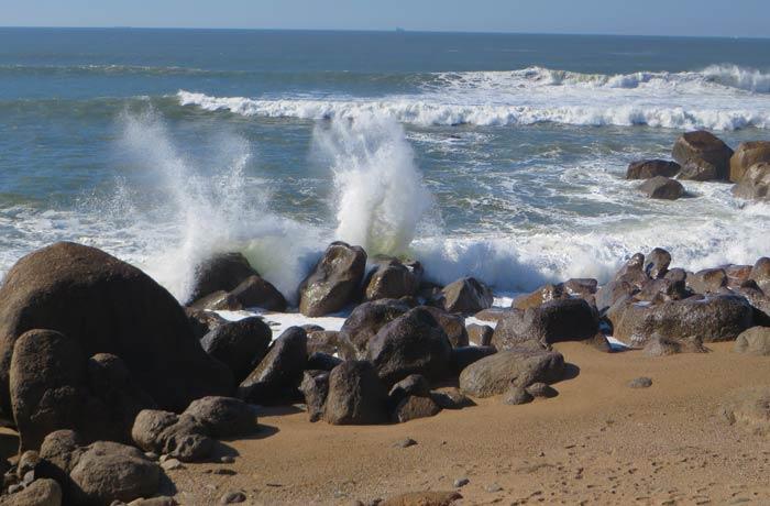 Olas rompiendo contra las rocas en el tramo final de la pasarela