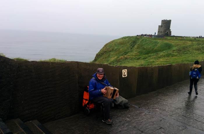 Simpático músico en los acantilados de Moher una semana en Irlanda