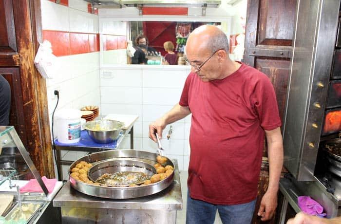 Un hombre cocina faláfel en Acre Israel por libre