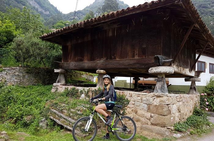 Estefanía ante un hórreo en Villanueva Senda del Oso en bici