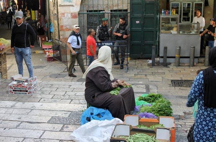 Una mujer musulmana vende verdura junto a un puesto policial israelí en el barrio musulmán qué ver en Jerusalén
