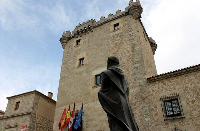 Torreón de los Guzmanes y escultura de San Juan de la Cruz Ávila en un día