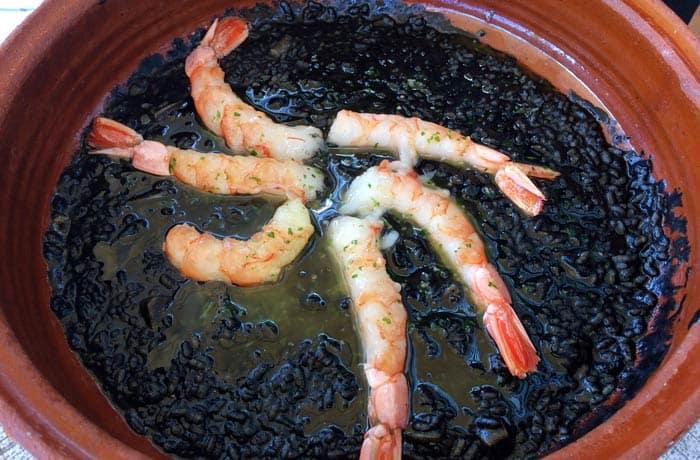 Arroz negro en su cazuela de barro comer en Menorca
