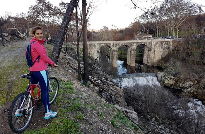 Con la bicicleta, junto al puente sobre el río Mondego