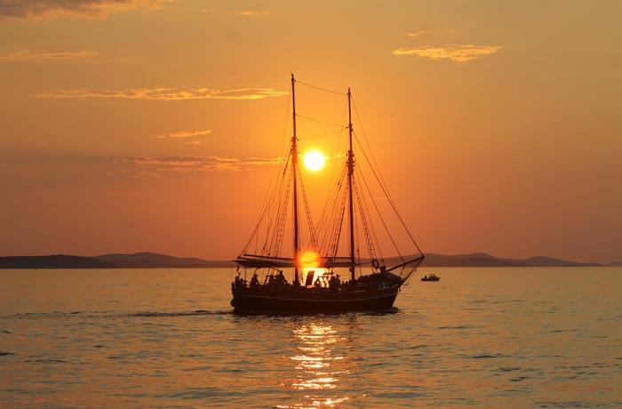 Un barco de vela pasar por delante del sol durante el atardecer en Zadar