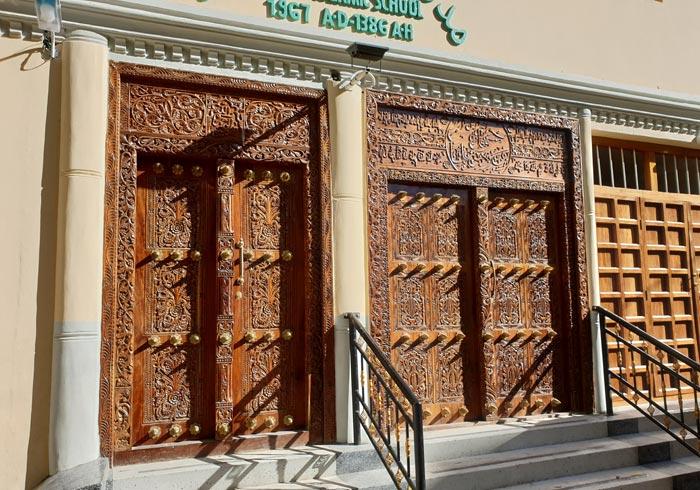 Puerta árabe con pasajes del Corán labrados en la madera